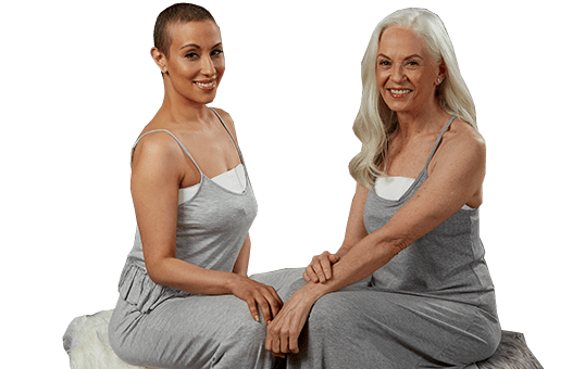 Two smiling women wearing EZBRA's and gray pajamas